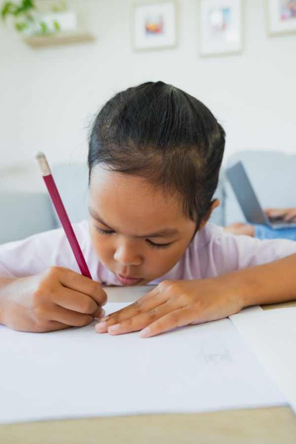 young girl writing on white paper with a pencil