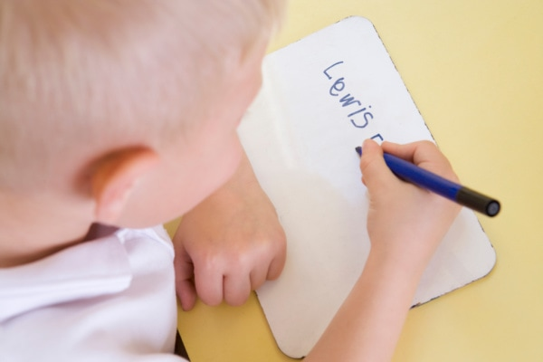 little boy writing his name on a small whiteboard